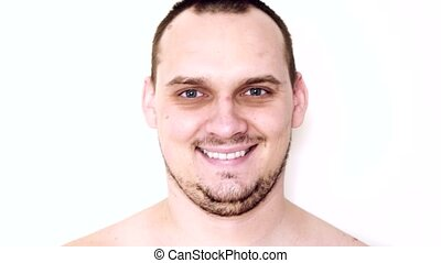 Closeup of smiling young man looking at camera isolated on...