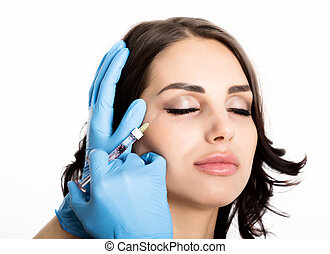 young woman gets beauty injection in eye and lips area from...