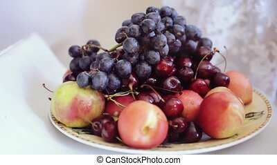 Man's hand taking fruit from plate with grape cherries and...