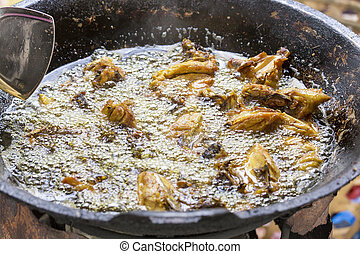 Fried Chicken Cooking in an Iron Skillet; Asia