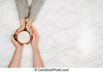 Couple holding hands with coffee white marble table, top view