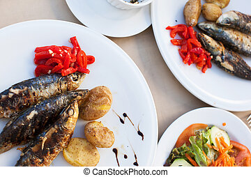 Fried sardines served with vegetables on plates close-up