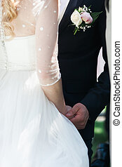 The groom holds the bride hands during the ceremony close-up