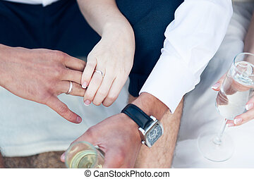 Newlyweds with glasses of champagne on hand close-up