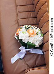 Wedding bouquet on a leather car seat close-up