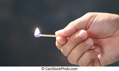 Holding Burning Match - Mans hand holds a burning stick...