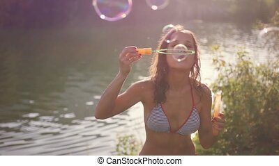 Beautiful fun young brunette woman blowing bubbles on a...