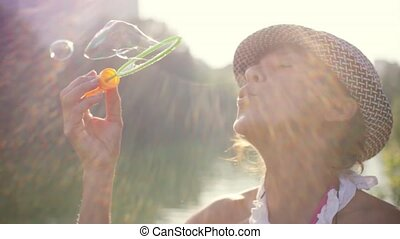 Beautiful mature woman in hat is blowing bubbles against the...