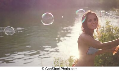 Beautiful young smiling brunette woman blowing bubbles on a beach in sunny day on summer.