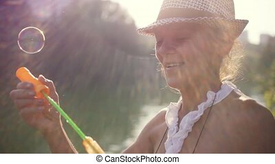 Beautiful caucasian mature woman in hat is blowing bubbles...