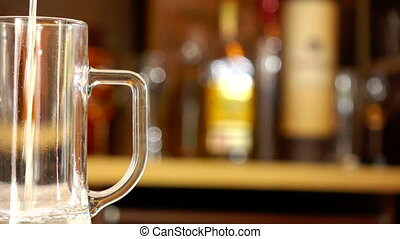 Pouring Beer Into Mug - Beer is pouring from the top into...