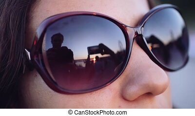 Close up of brunette young woman watch through glasses at...