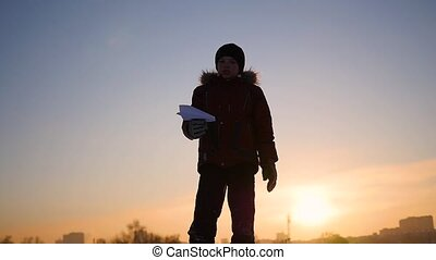child in the sky launches a paper airplane at sunset. Winter frosty day