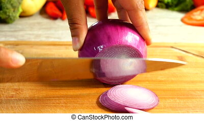 Slicing Red Onion In Slow Motion - Closeup of Female hands...