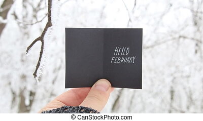 Hello February concept, inscription on a beautiful winter...