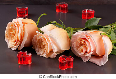 three beige rose with candles in the shape of heart on a dark wooden background
