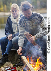 Couple Sitting By Bonfire On Lakeshore - Young couple...