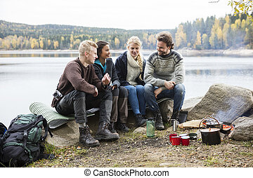 Friends Talking On Lakeshore During Camping - Happy...