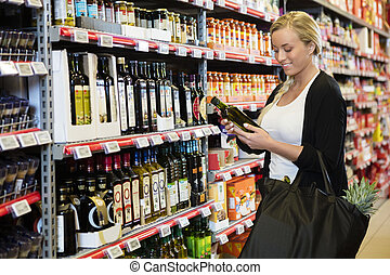 Young Woman Holding Olive Oil Bottle In Supermarket