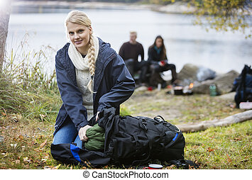 Young Woman Unpacking Backpack At Campsite - Portrait of...