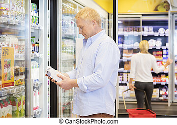 Man Holding Juice Packet In Grocery Store