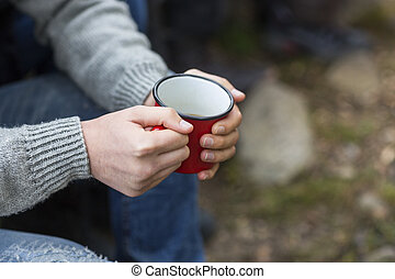 Man Holding Coffee Cup At Campsite - Midsection of young man...