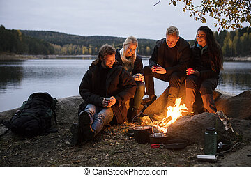 Friends With Coffee Cups Sitting By Campfire On Lakeshore -...