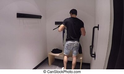 Young Man Trying on Clothes in Clothing Store - Young...