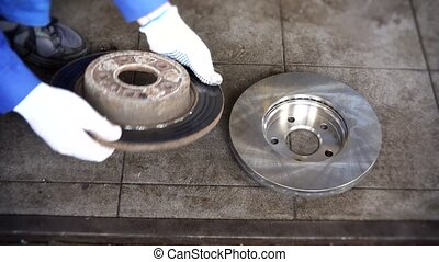 Mechanic man hands compare old worn brake disk with new object.