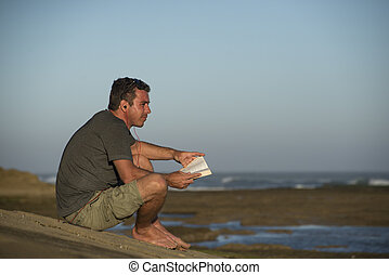 Man with Earphones and Book by Ocean - A man sits on a rock...