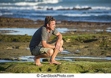 Man on haunches by rockpool - A middle aged man sits on his...