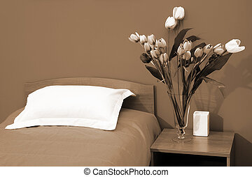 bed with an coverlet - Beautiful tulips at a bed with an...