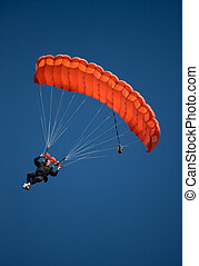 Red parachute against blue sky - Parachuter descending with...