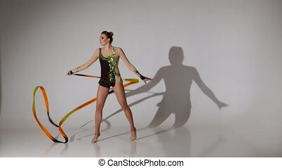 Rhythmic gymnast sit on one leg on the string. White...