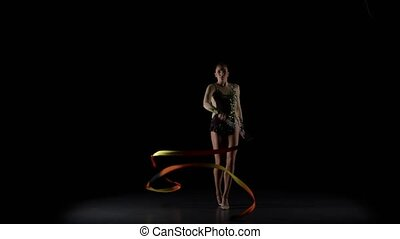 Gymnast gracefully move with a ribbon in his hands. Black...