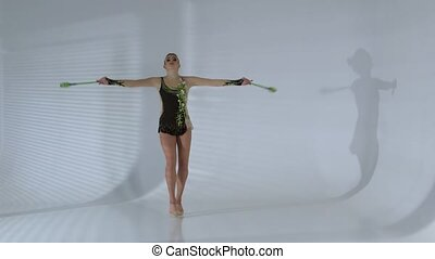 Girl gymnast doing acrobatic movement with a mace in his hand. White background