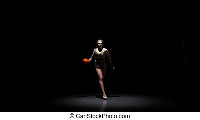 Gymnast with the ball in his hands doing acrobatic moves. Black background