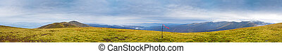 Autumn mountain panorama with red flag on the peak