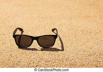 Black sunglasses on the beach