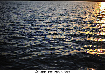 reflection of light on water surface in sunset