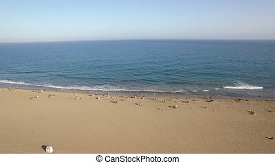 Aerial view of people on the ocean coast - Flying over the...