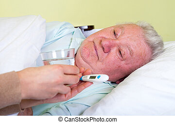 Bedridden elderly man having high temperature - Picture of a...