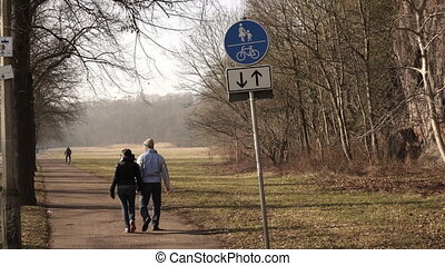 Couple Walking In Park Away From Sign - A male and female...