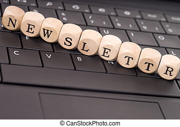 Newsletter - Keyboard and wooden cubes with the word...