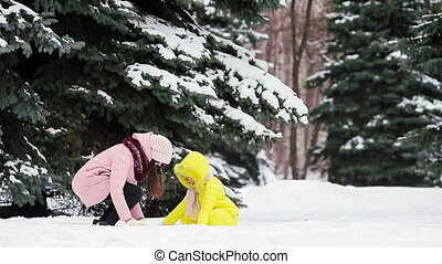 Happy mother and kid enjoy winter snowy day and playing...