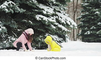 Family of mother and daughter enjoy winter snowy day and...