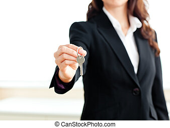 Close-up of a confident businesswoman holding a key against...