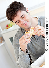 Delighted man eating bread in the kitchen at home