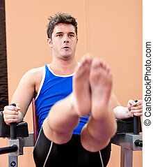 Muscular young man exercising in a fitness center