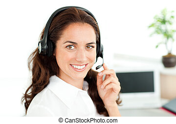 Smiling woman looking at the camera wearing a headset...